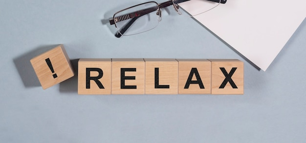 Relaks słowo napisane na drewnianych blokach kostki na biurowym stole