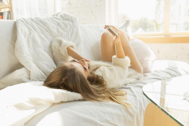 Relaks w domu. piękna młoda kobieta, leżąc na kanapie w domu z ciepłym światłem słonecznym