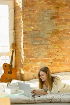 Relaks w domu. piękna młoda kobieta, leżąc na materacu z ciepłym światłem słonecznym. kaukaska blond modelka ma weekend na odpoczynek