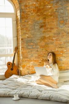Relaks w domu. piękna młoda kobieta, leżąc na materacu z ciepłym światłem słonecznym.
