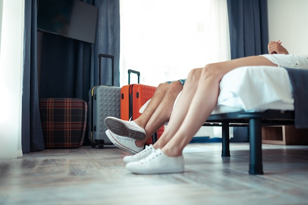 Relaks w hotelu. nogi małżeństwa leżące na łóżku w pokoju hotelowym pierwszego dnia wakacji.