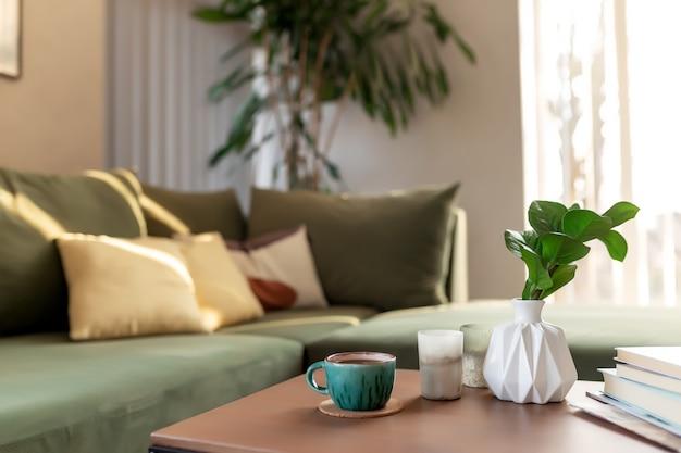 Relaks w komfortowym domu ze świecami, filiżanką kawy, książkami i wazonem z zamioculcas przy drewnianym stole. zielona sofa z żółtymi poduszkami. promienie słońca.