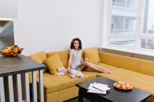 Relaks w nowoczesnym mieszkaniu zadowolonej, szczęśliwej młodej kobiety odpoczywającej na pomarańczowej kanapie. magazyn, filiżanka herbaty, domowe zwierzaki, radosny nastrój, uśmiech, prawdziwe emocje
