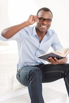 Relaks ze swoją ulubioną książką. wesoły młody afrykanin w niebieskiej koszuli, trzymający książkę i patrzący w kamerę, siedząc na schodach z filiżanką kawy obok niego