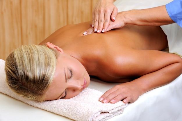Relaksacyjny masaż dla młodej kobiety w gabinecie kosmetycznym