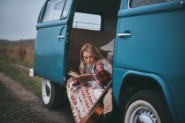 Relaksując się ze swoją ulubioną książką. atrakcyjna młoda kobieta przykryta kocem czytając książkę siedząc wewnątrz mini van niebieski w stylu retro niebieski