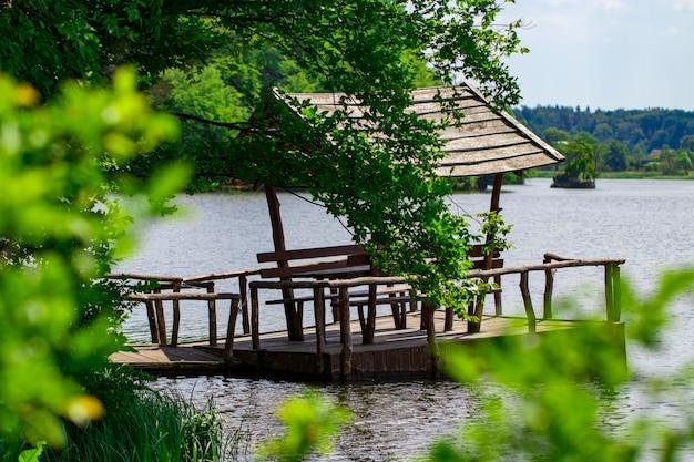 Relaksująca altana zbudowana nad rzeką na tle lasu.