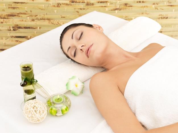 Relaksująca biała kobieta w salonie kosmetycznym spa. terapia rekreacyjna. odpoczywająca kobieta z zamkniętymi oczami