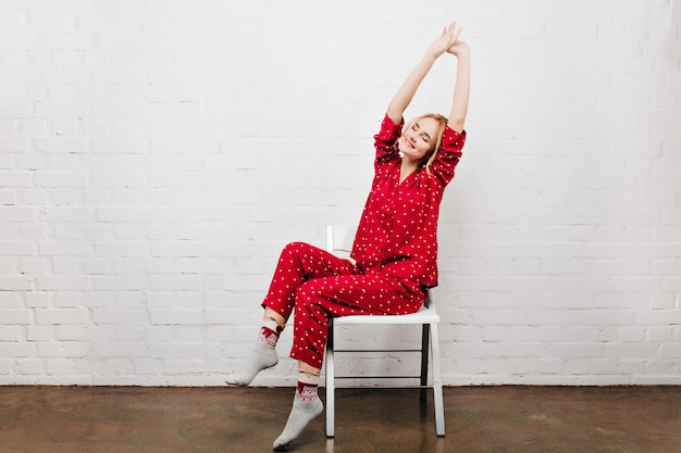 Relaksująca blondynka rozciąganie siedząc na krześle. zadowolona młoda dama w czerwonej koszuli nocnej pozuje na białej ścianie.