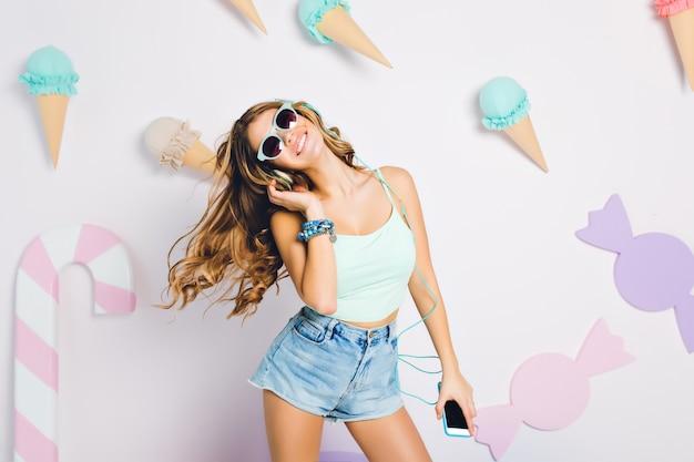 Relaksująca dziewczyna z długimi lśniącymi lokami tańczy w swoim pokoju z pastelowym wnętrzem, trzymając w ręku telefon komórkowy. portret mrożącej krew w żyłach młodej kobiety noszącej jasnoniebieski podkoszulek i okulary przeciwsłoneczne.