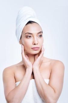 Relaksująca kąpiel. ładna młoda kobieta z włosami zawiniętymi w ręcznik turban i ubrana w biały ręcznik, trzymając twarz w dłoniach po gorącej kąpieli