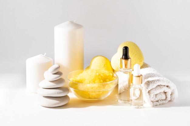 Relaksująca kompozycja produktów do kąpieli z żółtymi bombkami w kształcie serca, skrabem z soli morskiej, serum do ciała, świecami, ręcznikiem i kamiennym stosem na lekkiej ścianie. relaks, spa i koncepcja leczenia ciała.