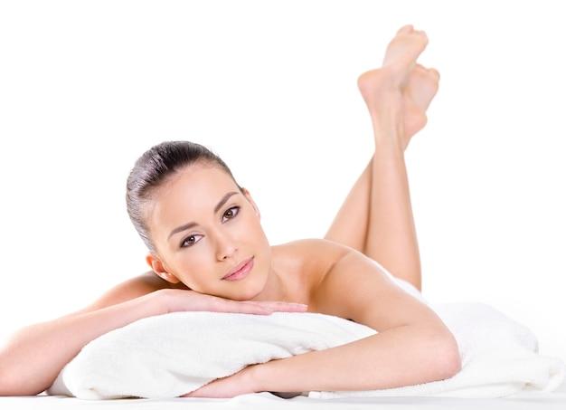 Relaksująca młoda piękna kobieta z świeżą skórą - białe tło. leżąc na łóżku