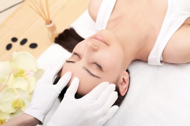 Relaksująca piękna kobieta ma masaż dla jej skóry na twarzy w piękno salonie