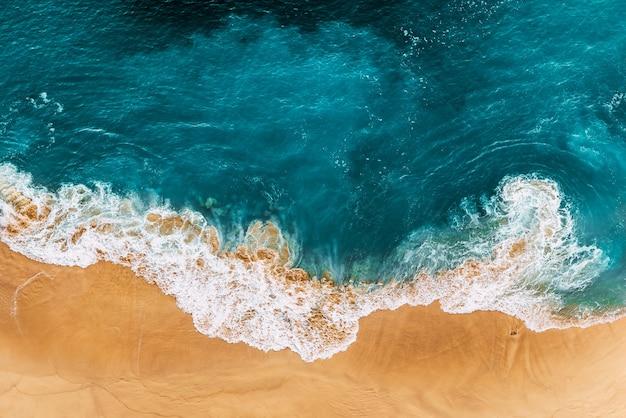 Relaksująca scena na plaży z lotu ptaka, letnie wakacje wakacje szablon transparent. fale surfują z niesamowitą błękitną laguną oceanu, brzegiem morza, wybrzeżem. idealny widok z góry z lotu ptaka. spokojna jasna plaża, wybrzeże