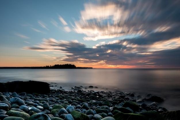 Relaksująca scena wybrzeża pod zachmurzonym niebem i zachodzącym słońcem w