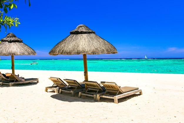Relaksujące tropikalne wakacje, leżaki i parasole na białej, piaszczystej plaży i turkusowym morzu