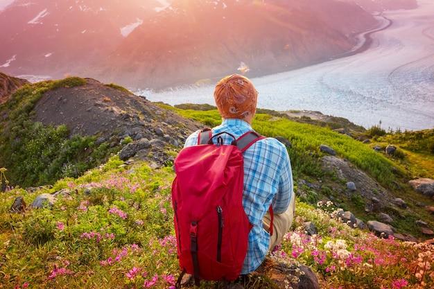 Relaksujący człowiek w górach o wschodzie słońca