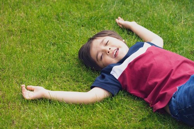 Relaksujący dziecko zamyka jego oczy i śmia się podczas gdy kłamający na zielonej trawie w parku