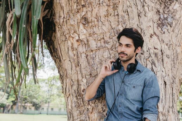 Relaksujący mężczyzna z słuchawkami w parku