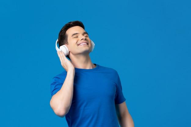 Relaksujący młody człowiek słucha muzyki od hełmofonów z zamkniętymi oczami
