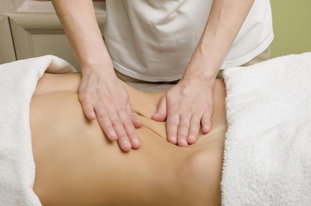 Relaksujący profesjonalny masaż kobiecego brzucha w salonie.