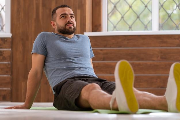 Relaksujący siedzenie oparty na ramionach młody szczęśliwy fitness facet robi ćwiczenia rozciągające w domu