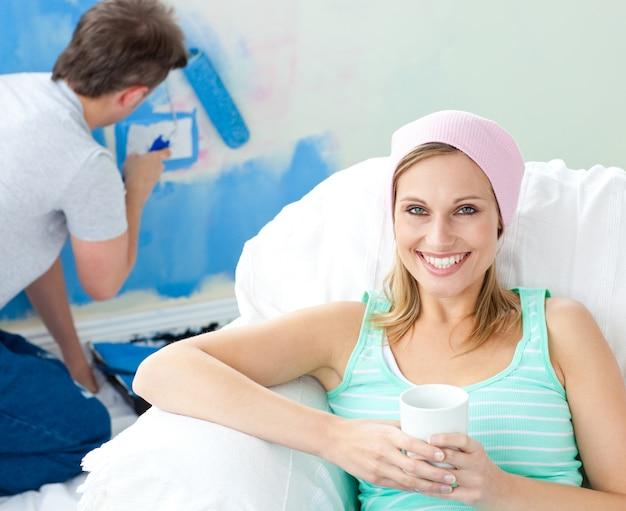 Relaksujący uśmiechnięty kobiety obsiadanie na kanapie patrzeje kamerę
