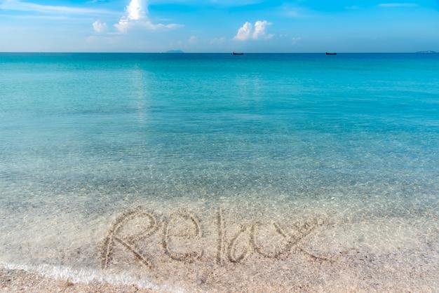 Relaksuje ręcznie pisany na piaskowatej plaży z niebieskim niebem.