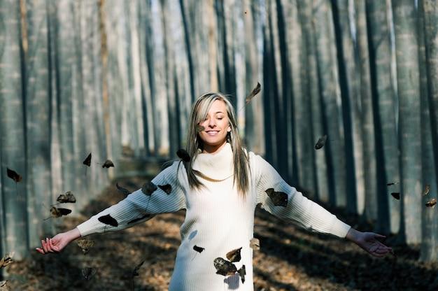 Relaxed kobieta bawi się z liśćmi w parku