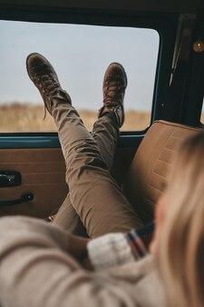 Relaxing... zbliżenie na tył młodej kobiety odpoczywającej, leżącej na przednim siedzeniu pasażera w samochodzie w stylu retro