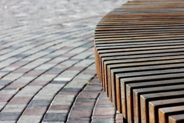 Reliefowa konstrukcja drewnianej ławki w połączeniu z dekoracyjną kostką brukową