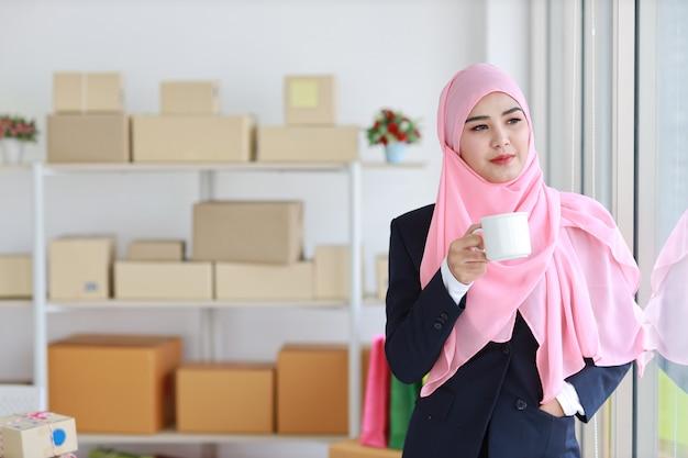 Religijna azjatykcia muzułmańska kobieta pije kawę, uśmiecha się i różowi szalika na głowie z pakunku pudełka dostawy tłem w błękitnym kostiumu. początkowa mała firma mśp niezależna dziewczyna pracuje w domu z radosną miną