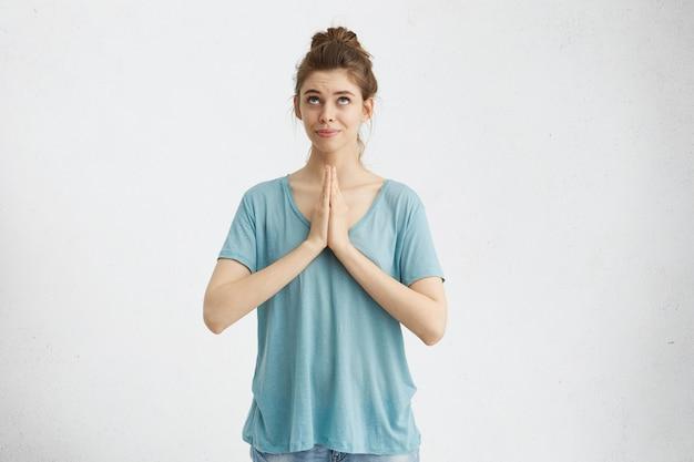 Religijna dziewczyna z włosami zebranymi w węzeł ściska dłonie i patrzy w górę, modląc się do boga, błagając o przebaczenie lub prosząc o spełnienie swojego marzenia. ludzkie emocje i uczucia