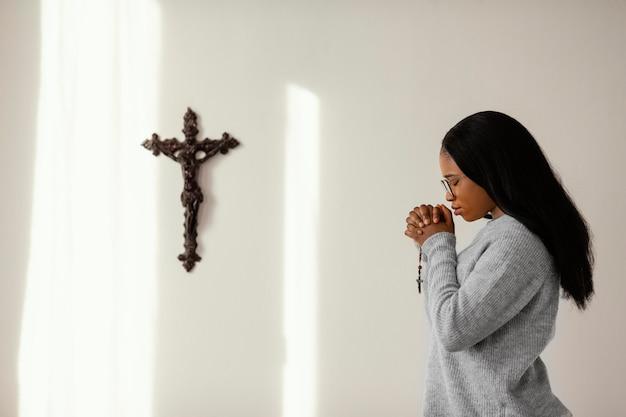 Religijna kobieta modląca się z różańca w domu
