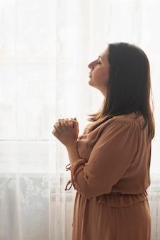 Religijna kobieta modli się w domu