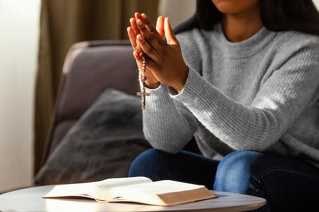 Religijna kobieta modli się z różańcem