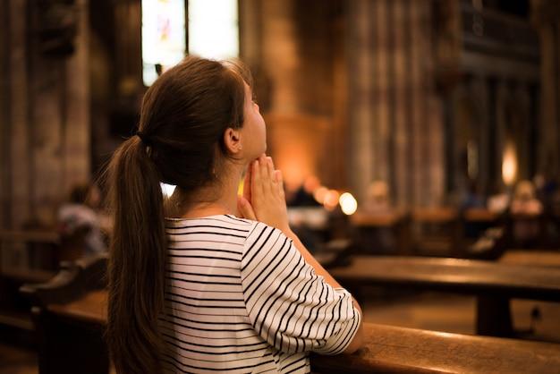 Religijna młoda kobieta siedzi na ławce w kościele katolickim modląc się