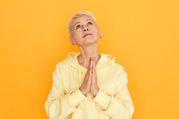 Religijna nieszczęśliwa emerytka z pełnymi nadziei oczami pozującymi odizolowanymi, trzymająca się za ręce, patrząc w górę, modląc się, błagając, prosząc boga o pomoc i wskazówki, przygnębiona w ciężkich czasach