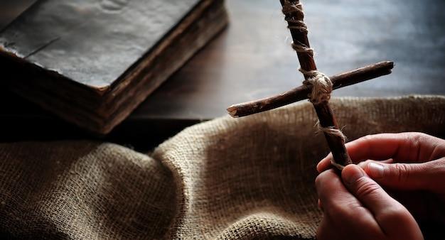 Religijna stara księga na drewnianym stole. krzyż religijny przewiązany sznurem i jutą obok biblii. uwielbienie, grzechy i modlitwa.