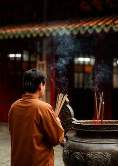 Religijny mężczyzna w świątyni z płonącym kadzidłem