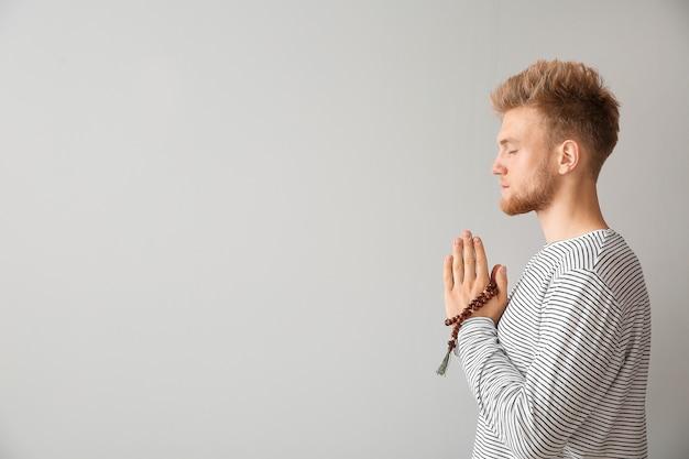 Religijny młody człowiek modlący się do boga na szaro