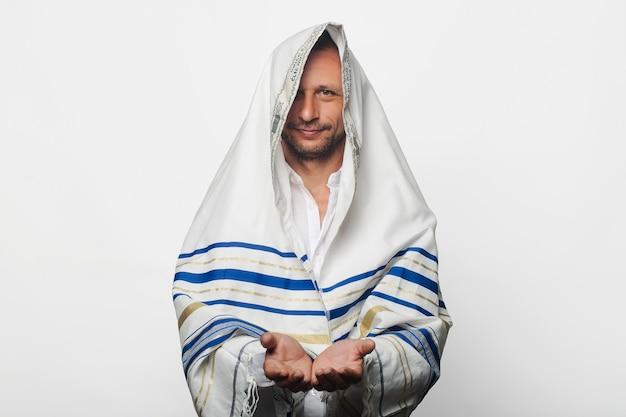 """Religijny żyd owinięty talitem modlitewnym szalem z napisem po hebrajsku """"baruch atah adonai"""" z dłońmi złożonymi dłońmi przyjmującymi lub dającymi gest. żydowska piątkowa modlitwa poranna"""