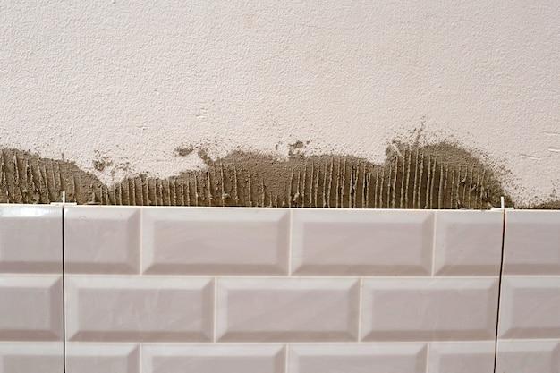 Remont domu, układanie płytek ceramicznych na ścianie.