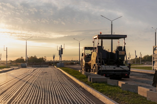 Remont dróg i układanie asfaltu specjalistyczną maszyną wieczorem na tle zachodzącego nieba. w godzinach wieczornych kostkarka pracuje naprawiając nawierzchnię drogi.