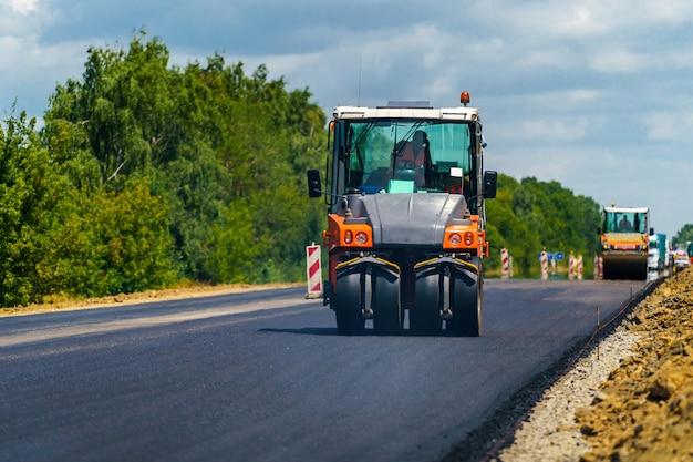 Remont dróg, zagęszczarka układa asfalt. ciężkie maszyny specjalne. rozściełacz asfaltu w eksploatacji. widok z boku. zbliżenie.