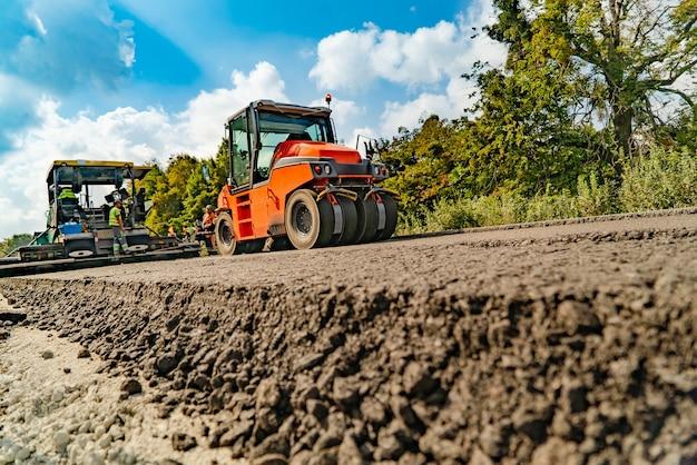 Remont dróg, zagęszczarka układa asfalt.