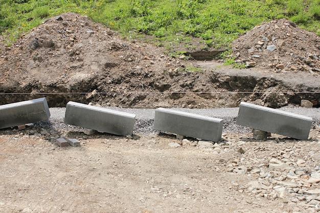 Remont drogi. układanie nowego krawężnika przed asfaltowaniem. roboty drogowe. nowe krawężniki gotowe do montażu.