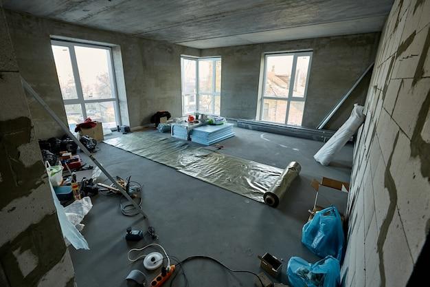 Remont mieszkania w wieżowcu w budowie przestronny pokój z dużymi plastikowymi oknami materiały budowlane nowoczesne narzędzia i sprzęt