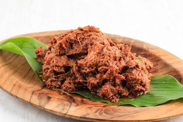 Rendang daging suwir, pikantny gulasz wołowy z padang w indonezji. na białym tle na drewnianym talerzu, biały stół